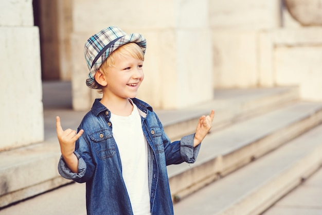 Weinig jongen die het teken van de zwaar metaalrots in openlucht afschildert. jeugd levensstijl concept.