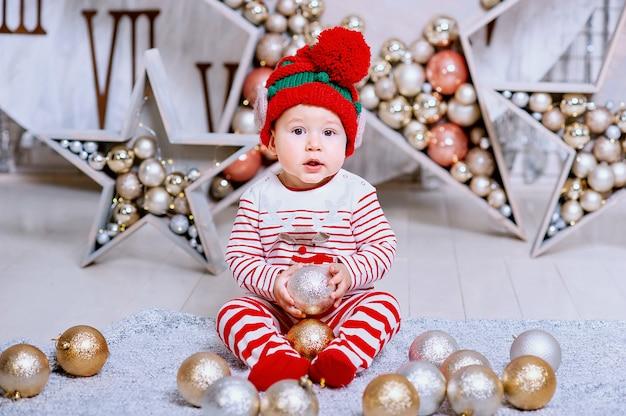 Weinig jongen die in elfhoed op een de boomdecoratie van de kerstmisholding wachten,