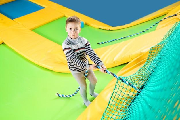 Weinig jongen die in trampolinecentrum spelen die en met kabel springen beklimmen