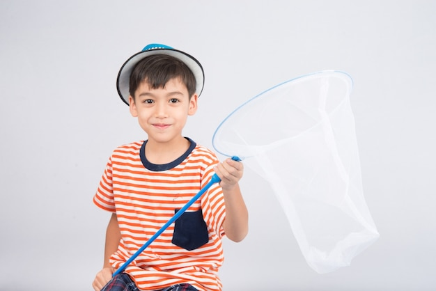 Weinig jongen die insectennet op witte muur neemt