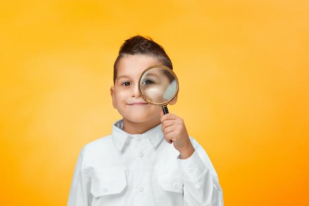 Weinig jongen die meer magnifier dicht omhoog kijken gebruiken
