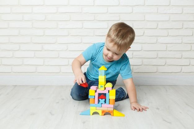 Weinig jongen die met aannemer op witte achtergrond speelt. babyjongen speelt blokken speelgoed