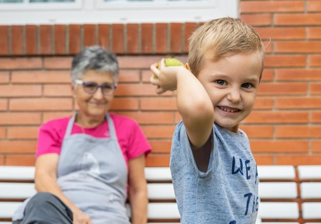 Weinig jongen die met de bal speelt terwijl zijn grootmoeder hem bekijkt