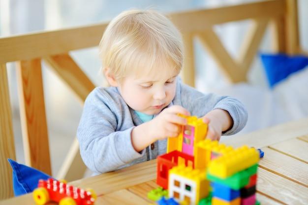 Weinig jongen die met kleurrijke plastic blokken bij kleuterschool speelt of thuis