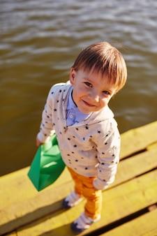 Weinig jongen die met stuk speelgoed document schip door het meer speelt