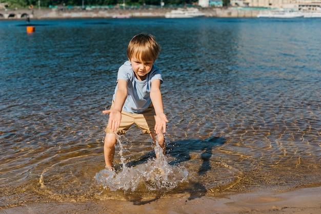 Weinig jongen die met water op kust speelt
