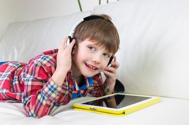 Weinig jongen die op bed legt speelt de tablet