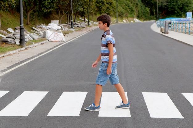 Weinig jongen die op de weg kruist