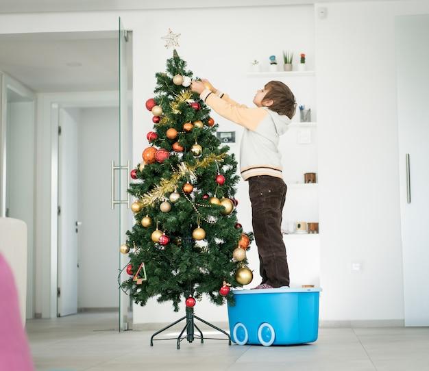 Weinig jongen die op speelgoeddoos beklimt om kerstboom te verfraaien