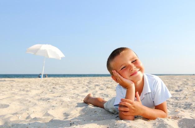 Weinig jongen die op strand geniet