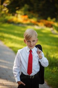 Weinig jongen die pak en rode band op aardachtergrond draagt