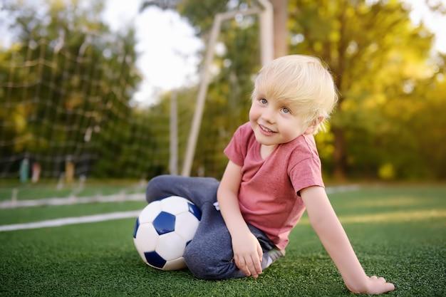 Weinig jongen die pret heeft die een voetbal / een voetbalspel op de zomerdag speelt. actief buiten spel / sport voor kinderen.