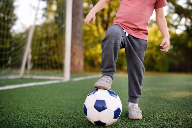 Weinig jongen die pret heeft die een voetbal / een voetbalspel op de zomerdag speelt.