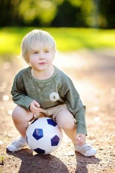 Weinig jongen die pret heeft die een voetbal / een voetbalspel op de zomerdag speelt