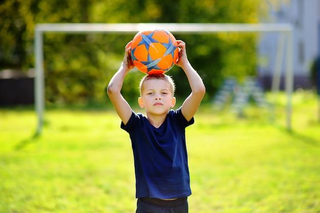 Weinig jongen die pret heeft die een voetbalspel op zonnige de zomerdag speelt