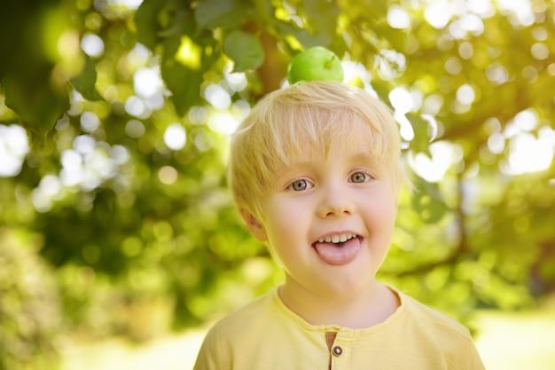 Weinig jongen die pret met appel op hoofd in binnenlandse tuin heeft