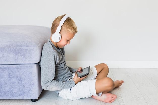 Weinig jongen die pret met tablet en oortelefoons heeft