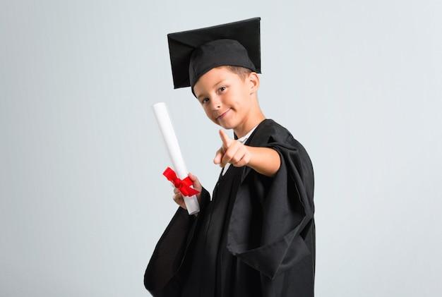 Weinig jongen die puntenvinger naar u op grijze achtergrond een diploma behalen