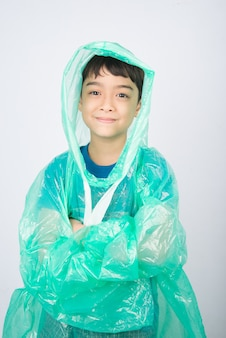 Weinig jongen die regenjas op witte muur draagt