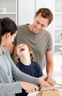 Weinig jongen die terwijl zijn moeder brood snijdt lacht
