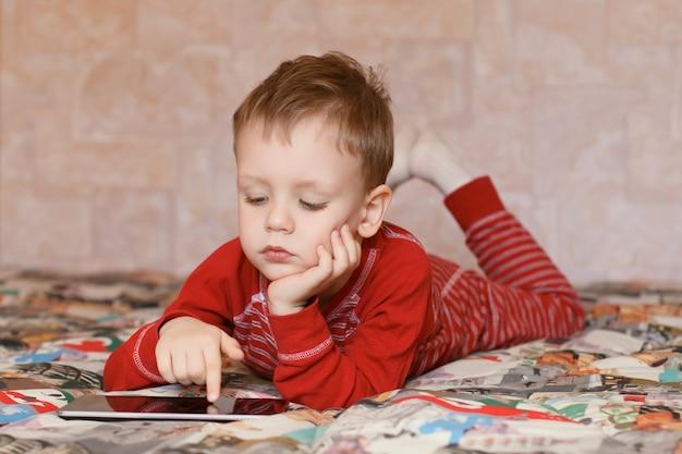 Weinig jongen die thuis op de tabletcomputer speelt