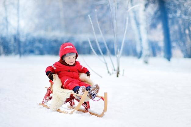 Weinig jongen die van een arrit geniet. kindersleeën. peuterjong geitje die een slee berijden. kinderen spelen buiten in de sneeuw. kinderen slee in winter park. buiten actief plezier voor familievakantie.