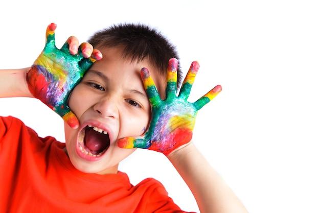 Weinig jongen die van zijn schilderend met handen genieten die in kleurrijke verf op witte achtergrond worden geschilderd