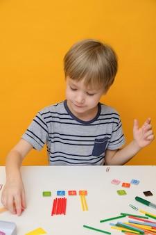 Weinig jongen die voor basisschool voorbereidingen treft die eenvoudige wiskundeoefeningen doet