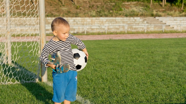 Weinig jongen die voor th doelen wacht om te voetballen met zijn schoenen in de ene hand en een voetbal in de andere