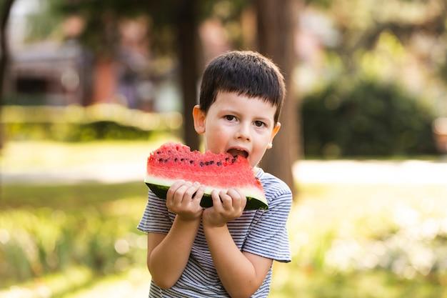 Weinig jongen die watermeloen heeft openlucht