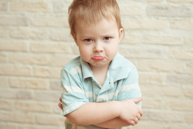 Weinig jongen die zich met gevouwen handen tegen een bakstenen muur bevindt. het concept van wrok, frustratie, teleurstelling, verdriet