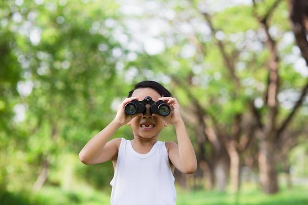 Weinig jongen die zich op een groen grasrijk gebied bevindt dat het omringende bos met verrekijker aftast terwijl hij het platteland verkent