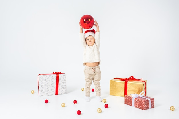 Weinig jongen die zich tussen giften bevindt en grote rode kerstmisbal in handen houdt. geïsoleerd op witte achtergrond vakantie, kerstmis, nieuwjaar, kerstmisconcept.