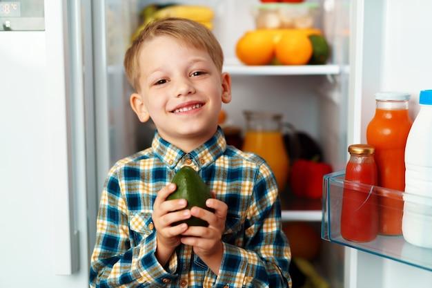 Weinig jongen die zich voor open koelkast bevindt en voedsel kiest