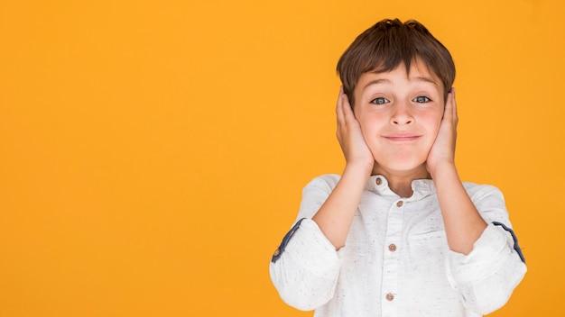 Weinig jongen die zijn oren behandelt met exemplaarruimte