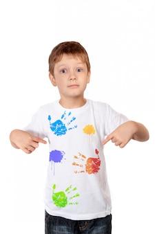 Weinig jongen die zijn vingers op een witte t-shirt richt