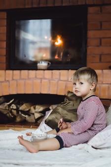 Weinig jongen door het vuur en warme chocolademelk met marshmallows
