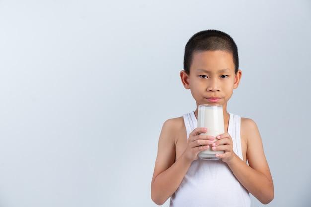Weinig jongen drinkt glas melk op witte muur.