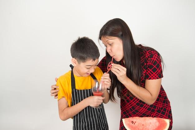 Weinig jongen drinkt vruchtensapwatermeloen met moeder