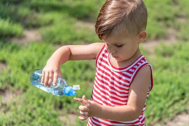 Weinig jongen drinkt water uit een fles op een hete dag die op de weide speelt