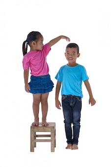 Weinig jongen en meisje die hun hoogte meten die op witte achtergrond wordt geïsoleerd