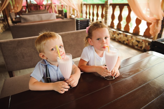 Weinig jongen en meisje die milkshakes in een koffie in openlucht drinken.