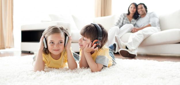 Weinig jongen en meisje die op de vloer met hoofdtelefoons spelen