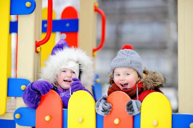 Weinig jongen en meisje in de winterkleren die pret in in openlucht speeltuin hebben
