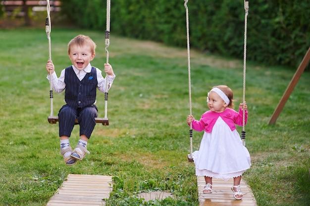 Weinig jongen en meisje rijden in het park op een schommel