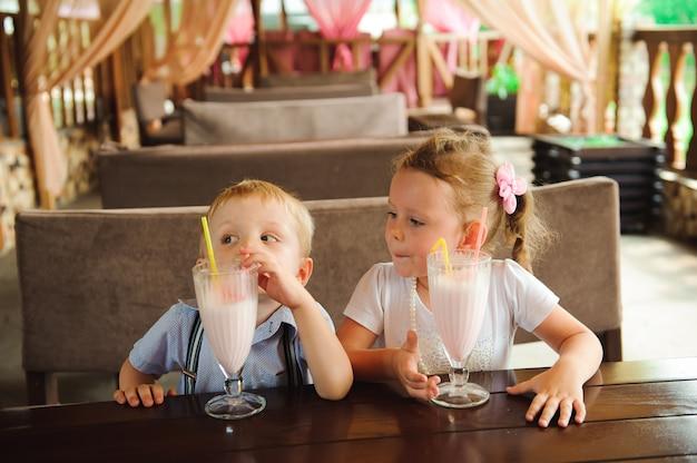Weinig jongen en meisjes het drinken milkshakes in een koffie in openlucht.