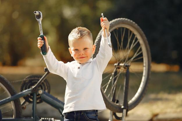 Weinig jongen herstelt zijn fiets in een park