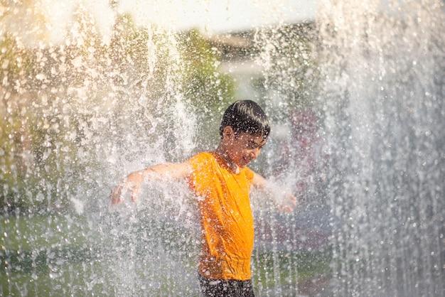 Weinig jongen het spelen water laat vallen fontein onder de doek en de paraplu