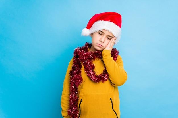 Weinig jongen het vieren kerstmisdag die een geïsoleerde santahoed draagt die zich verveelt, vermoeid en behoefte heeft aan een ontspannen dag.