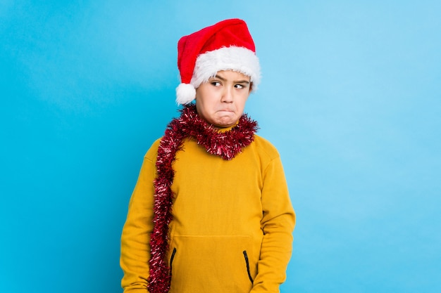 Weinig jongen het vieren kerstmisdag die een geïsoleerde verwarde santahoed draagt, voelt twijfelachtig en onzeker.
